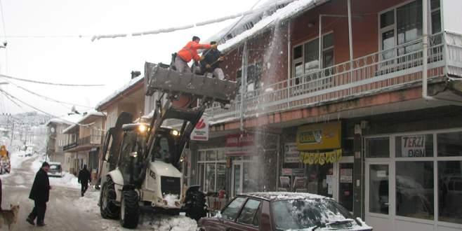 Keles'te kar sebebiyle çökebilecek çatılar temizleniyor