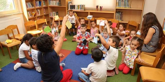 Çocuklar anneleriyle birlikte kütüphanede