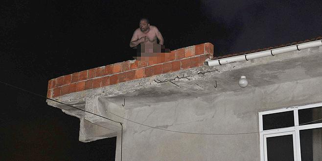 Evini yakıp, çıplak halde çatıya çıktı