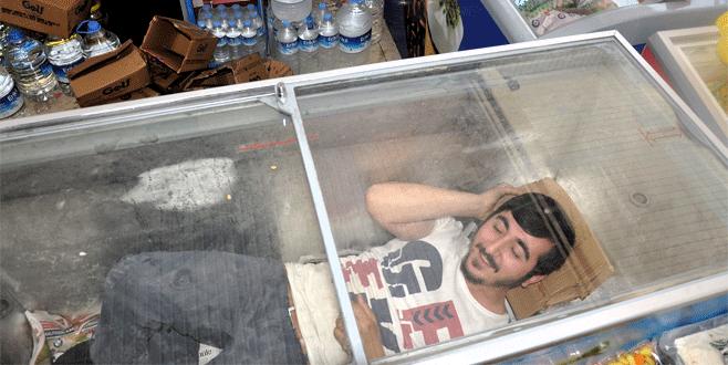 Sıcaktan bunalan esnaf dondurma dolabında serinliyor
