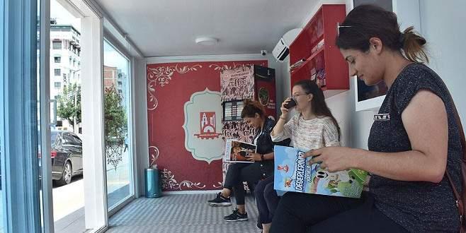 Otobüs beklerken kitap okuyup kahve içiyorlar