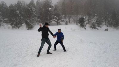 Buz tutan göletin üzerinde kar topu oynadılar