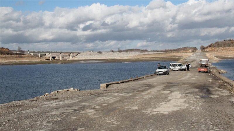 Barajdaki su seviyesi düşünce ortaya çıkan eski yoldan olta atıp balık avlıyorlar
